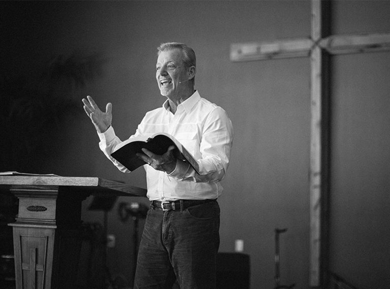 Worship Leader reading from bible during sermon